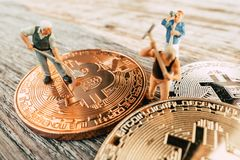 Bitcoin Mining miniature people digging. On valuable coin wood background stock image