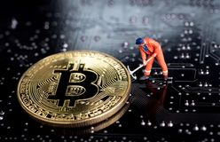 Bitcoin mining miniature worker, small figure holding mattock di. Gging on shiny golden Bitcoin crypto currency coin on electronics cyber look circuit board with Stock Photography