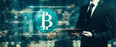 Bitcoin mit dem Geschäftsmann, der eine Tablette hält Lizenzfreies Stockfoto