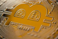 Bitcoin monet coin closeup. Bitcoin currency DOF on blue glass background. Gold metal curency symbol macro photo closeup stock photo