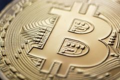 Bitcoin monet coin currency closeup. Bitcoin currency DOF on blue glass background. Gold metal curency symbol macro photo closeup royalty free stock images