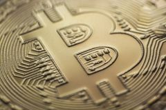Bitcoin monet coin currency closeup. Bitcoin currency DOF on blue glass background. Gold metal curency symbol macro photo closeup stock photography