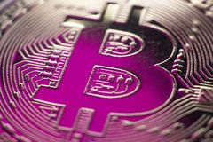 Bitcoin monet coin currency closeup on pink backlight. Bitcoin currency DOF on blue glass background. Gold metal curency symbol macro photo closeup royalty free stock images
