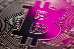 Bitcoin monet coin currency closeup in pink light. Bitcoin currency DOF on blue glass background. Gold metal curency symbol macro photo closeup royalty free stock photography