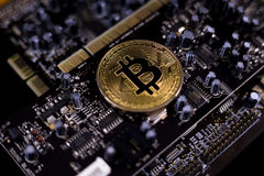 Bitcoin and motherboard. Bitcoin symbol on a motherboard Stock Photos