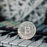 Bitcoin and music keyboard. Digital currency physical metal bitcoin coin and music keyboard. Cryptocurrency sound concept royalty free stock image