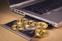 Bitcoin mynt över ett CD drev för bärbar dator` s Royaltyfri Fotografi