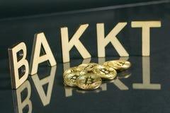 Bitcoin mynt framme av bakkttecknet som göras av trä med reflexion på tabellen arkivbild
