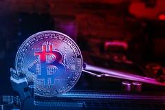 Bitcoin mynt med abstrakt rött glöd på bakgrunden av moderkortet och de röda blåa ljusen Symbol av crypto valuta - elektron royaltyfria bilder