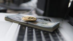 Bitcoin mynt med bärbara datorn och oss dollar Bitcoin guld- mynt på en bärbar dator för vit för bakgrund för dollarsedelkontor Royaltyfri Bild