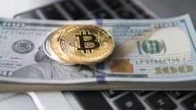 Bitcoin mynt med bärbara datorn och oss dollar Bitcoin guld- mynt på en bärbar dator för vit för bakgrund för dollarsedelkontor Royaltyfri Fotografi