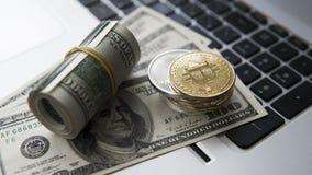 Bitcoin mynt med bärbara datorn och oss dollar Bitcoin guld- mynt på sedlar och bärbara datorn för en dollar Cryptocurrency Arkivfoton