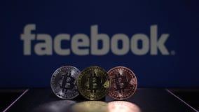 Bitcoin mynt med den bl?a sk?rmen f?r Facebook logo stock video