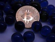 Bitcoin mynt mellan blåa glass marmor Royaltyfria Foton