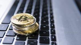 Bitcoin mynt på en överkant av andra crypto mynt på ett tangentbord av bärbara datorn Bitcoin guld- mynt Cryptocurrency investeri Arkivbilder