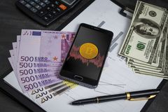 Bitcoin na telefonu screensaver wśród stosu dolary i eur zdjęcia stock