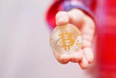 Bitcoin nas mãos de uma criança O menino guarda uma moeda do metal de c Imagem de Stock