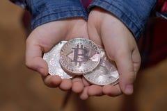 Bitcoin nas mãos de uma criança O menino guarda uma moeda do metal de c Fotografia de Stock Royalty Free
