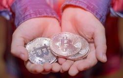 Bitcoin nas mãos de uma criança O menino guarda uma moeda do metal de c Fotos de Stock Royalty Free