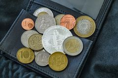 Bitcoin, national and euro coins on black leather wallet. stock photography