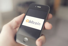 Bitcoin. The new digital cryptocurrency sweeping across the world, being utilized on a smartphone royalty free stock images