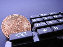 Bitcoin on numeric keyboard. Bitcoin on top of numeric keyboard computer part on black background Royalty Free Stock Photo