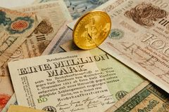Bitcoin phisical coin with old german money. Cash Inflation. Cryptocurrency concept background. Closeup with copy space. Bitcoin with old deutsch paper money Royalty Free Stock Images