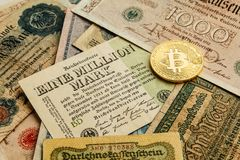 Bitcoin with old deutsch money. Inflation of paper money. Cryptocurrency concept background. Closeup with copy space. royalty free stock photos