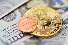 Bitcoin and one cent. Coin on US dollar bills, macro shot Royalty Free Stock Images