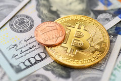 Bitcoin and one cent. Coin on US dollar bills, macro shot Royalty Free Stock Photos