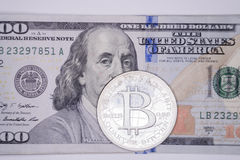 Bitcoin on one hundred. Bitcoin digital currency on top of single one hundred dollar bill Royalty Free Stock Images