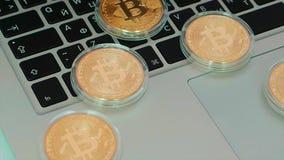 Bitcoin op laptop toetsenbord voorraad Dichte omhooggaand van het Bitcoinmuntstuk met laptop op achtergrond, cryptocurrencyconcep stock footage
