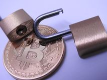 Bitcoin and brass padlocks. Bitcoin and open brass padlocks on gray background Stock Photography