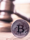 Bitcoin out of law concept. On background of gavel. Toned royalty free stock photography