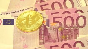 Bitcoin over pile of five hundred euro banknotes. Traditional money versus cryptocurrency concept Royalty Free Stock Photo