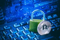 Bitcoin with padlock on computer motherboard. Crypto currency Internet data privacy information security concept. Blue toned image royalty free stock photos