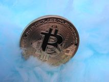 Bitcoin on cloud like blanket. Bitcoin pampered with an soft heavenly blue - white blanket Stock Photo