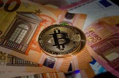 Bitcoin phisical versie van virtueel muntstuk over euro bankbiljetten stock afbeeldingen