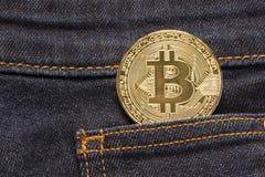 Bitcoin Physical Coin In Denim Pocket. Golden bitcoin physical coin in dark blue denim pocket Royalty Free Stock Photos