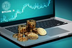 Bitcoin piles laying on computer with Bitcoin logo on-screen Stock Photography
