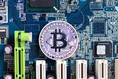 Bitcoin is placed on the motherboard, applicable to the business. Background concept, find the money via computer Royalty Free Stock Photo