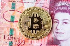 Bitcoin and 50 pound banknotes stock photos