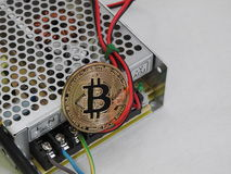 Bitcoin on power supply. With perforated metal background and power cable connections Stock Photos