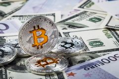 Bitcoin prägt auf Hintergrund von Banknoten von Dollar und von Euros Lizenzfreie Stockfotografie