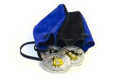 Bitcoin prägt das Legen auf weißen Hintergrund mit Lederbeutel stockbild