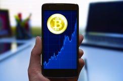 Bitcoin-Preis-Wachstumsdiagramm Symbol Cryptocurrency Bitcoin und Wachstumstabelle am Smartphoneschirm, Smartphone in der Hand Lizenzfreies Stockfoto