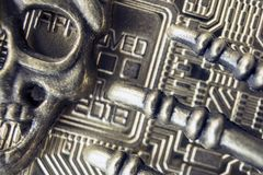 Bitcoin-2018 is raspy. Piracy. The metal face of the pirate skeleton and the bones of the fingers on the background of the reverse. Macro. Bitcoin-2018 is raspy Stock Photography
