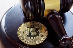 Bitcoin Regulation. BTC crypto coin and gavel on a desk. Bitcoin Regulation concept. BTC crypto coin and gavel on a desk royalty free stock image
