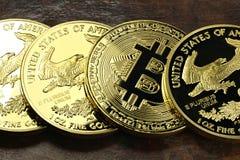 Bitcoin. In a row of 1 ounce American gold eagle bullion coins stock photos