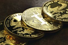 Bitcoin. In a row of 1 ounce American gold eagle bullion coins stock image